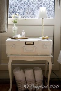 Side table with suitcase and wire basket with towels