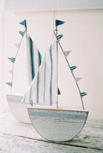 These are NOT on Etsy, but Matt said he'd make one for me. If he makes the base and creates a dowel, I can make a sail with left over fabric from the bunting. This sailboat can sit on the shelf above the change table.